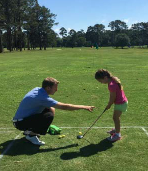An instructor helps a young golfer at a junior golf camp